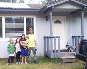 family standing next to home in alaska